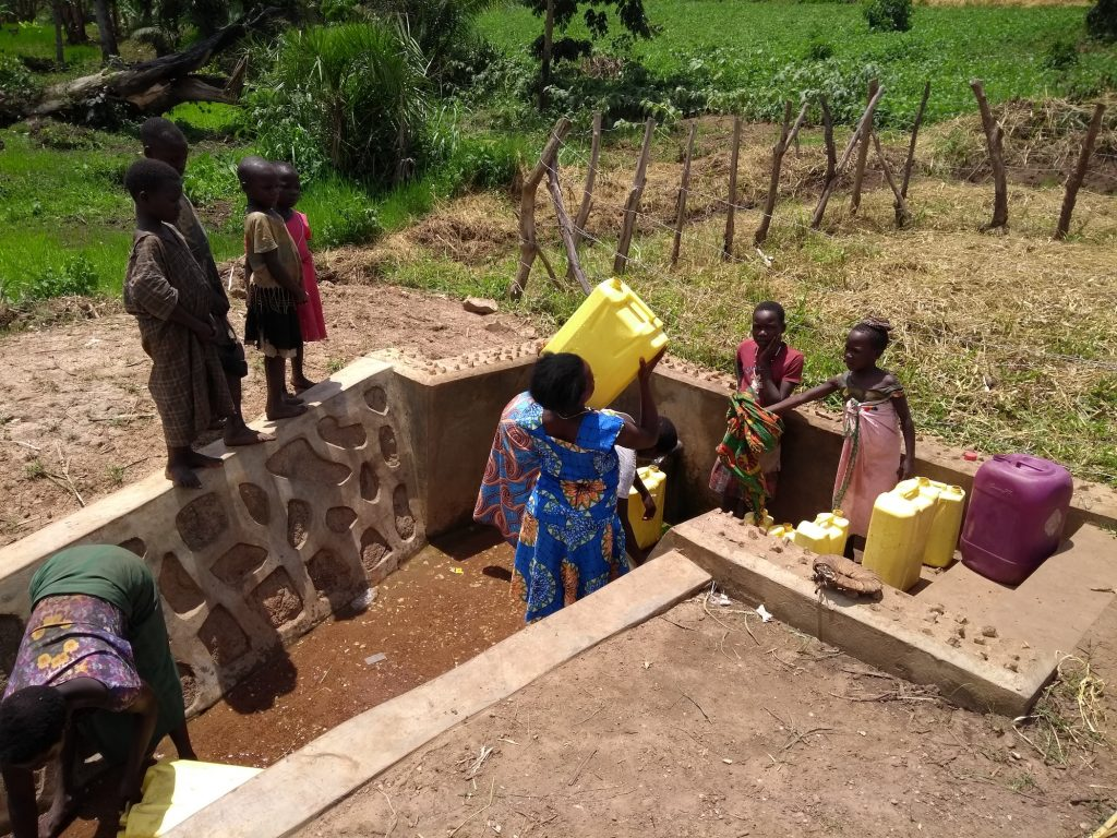The Water Project : uganda6088-lifting-filled-container-of-water-to-carry-home