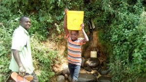 The Water Project:  Boy Fetching Water At The Spring