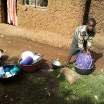 The Water Project: Musango Community, Mushikhulu Spring -  Child Washing Utensils With Spring Water