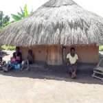 The Water Project: Karagalya Kawanga Community -  Nyamungu Grace And Her Children Seated Outside Of Her Hut