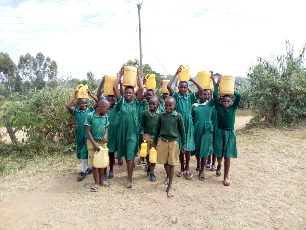 The Water Project : 4-kenya19173-students-arriving-at-school-with-water