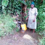 The Water Project: Bukhakunga Community, Ngovilo Spring -  Mrs Ngovilo Fetching Water