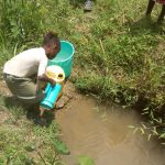The Water Project: Emaka Community, Ateka Spring -  Gabriel Fetching Water At The Spring