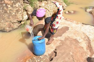 The Water Project:  Filling Container With Water From The River