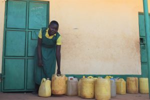 The Water Project:  Student Fetches Water From Containers In Front Of Classroom