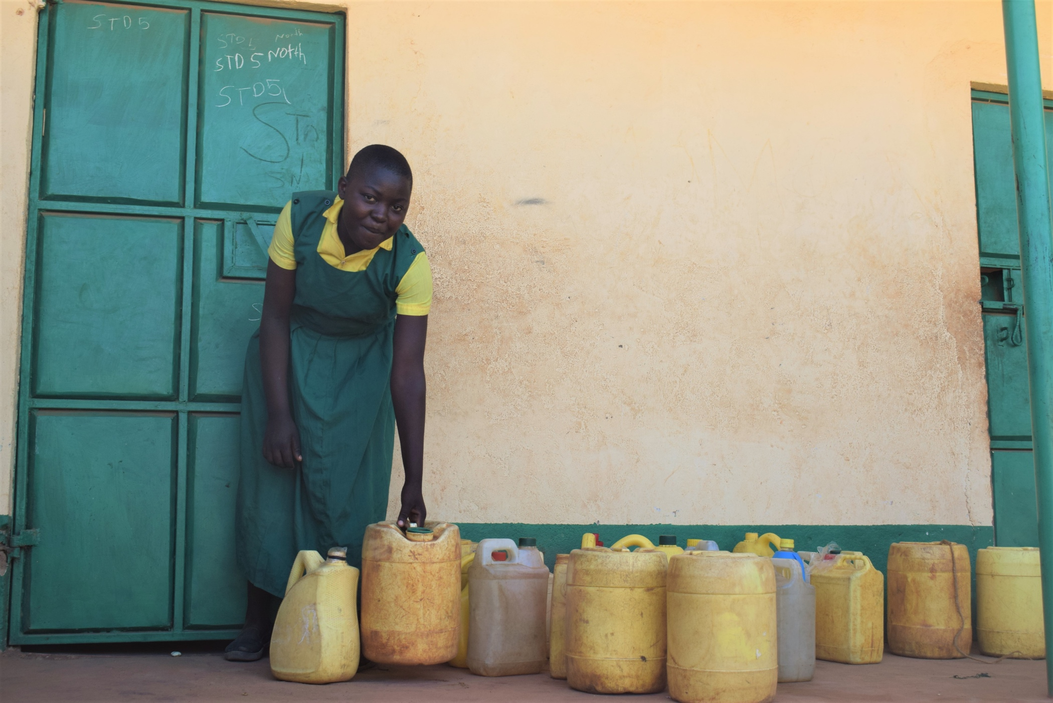 The Water Project : kenya19237-student-fetches-water-from-containers-in-front-of-classroom