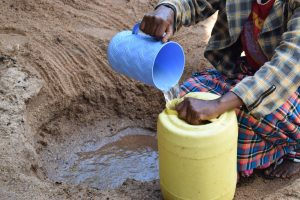 The Water Project:  Filling Plastic Container With Water From The Scoop Hole
