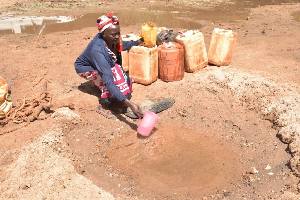 The Water Project : kenya19248-scooping-water-to-pour-into-container