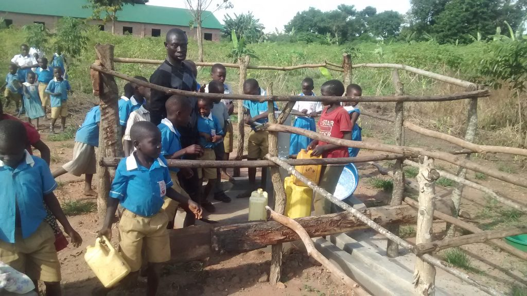 The Water Project : uganda18294-students-draw-water-from-completed-well