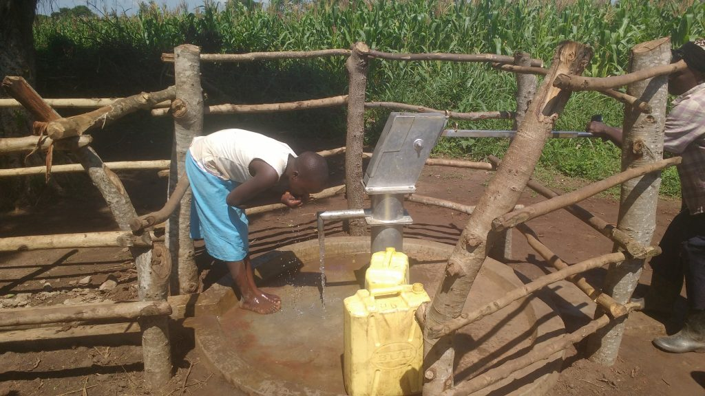 The Water Project : uganda18300-drinking-water-from-the-well