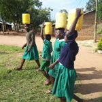 The Water Project: Ebutenje Primary School -  Carrying Water Back To School