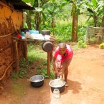 The Water Project: Mutao Community, Kenya Spring -  Agness Using Spring Water To Wash Dishes