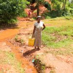 The Water Project: Mutao Community, Kenya Spring -  Woman By The Spring