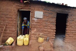 The Water Project:  Posing With Water Containers At Home