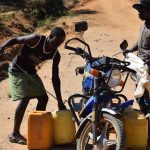 The Water Project: Tulimani Community A -  Preparing To Put Fetched Water Onto Motorbike