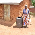 The Water Project: Mbiuni Community A -  Standing With Water Storage Container
