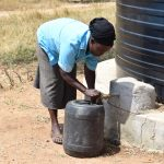 The Water Project: Kyamatula Secondary School -  Fetching Water From Small Plastic Tank