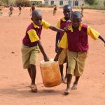 The Water Project: Nguluma Primary School -  Younger Students Carrying Water