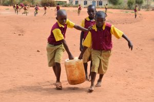 The Water Project:  Younger Students Carrying Water