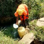 The Water Project: Chegulo Community, Sembeya Spring -  Mrs Ayieta Fetching Water