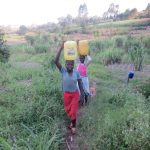 The Water Project: Ikonyero Community, Amkongo Spring -  Carrying Water