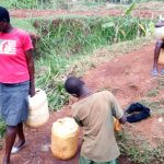 The Water Project: Kitulu Community, Kiduve Spring -  Waiting To Fetch Water