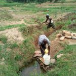 The Water Project: Shihingo Community, Inzuka Spring -  Fetching Water As The Man Behind Clears Drainage Channel As Advised