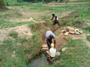 The Water Project:  Fetching Water As The Man Behind Clears Drainage Channel As Advised