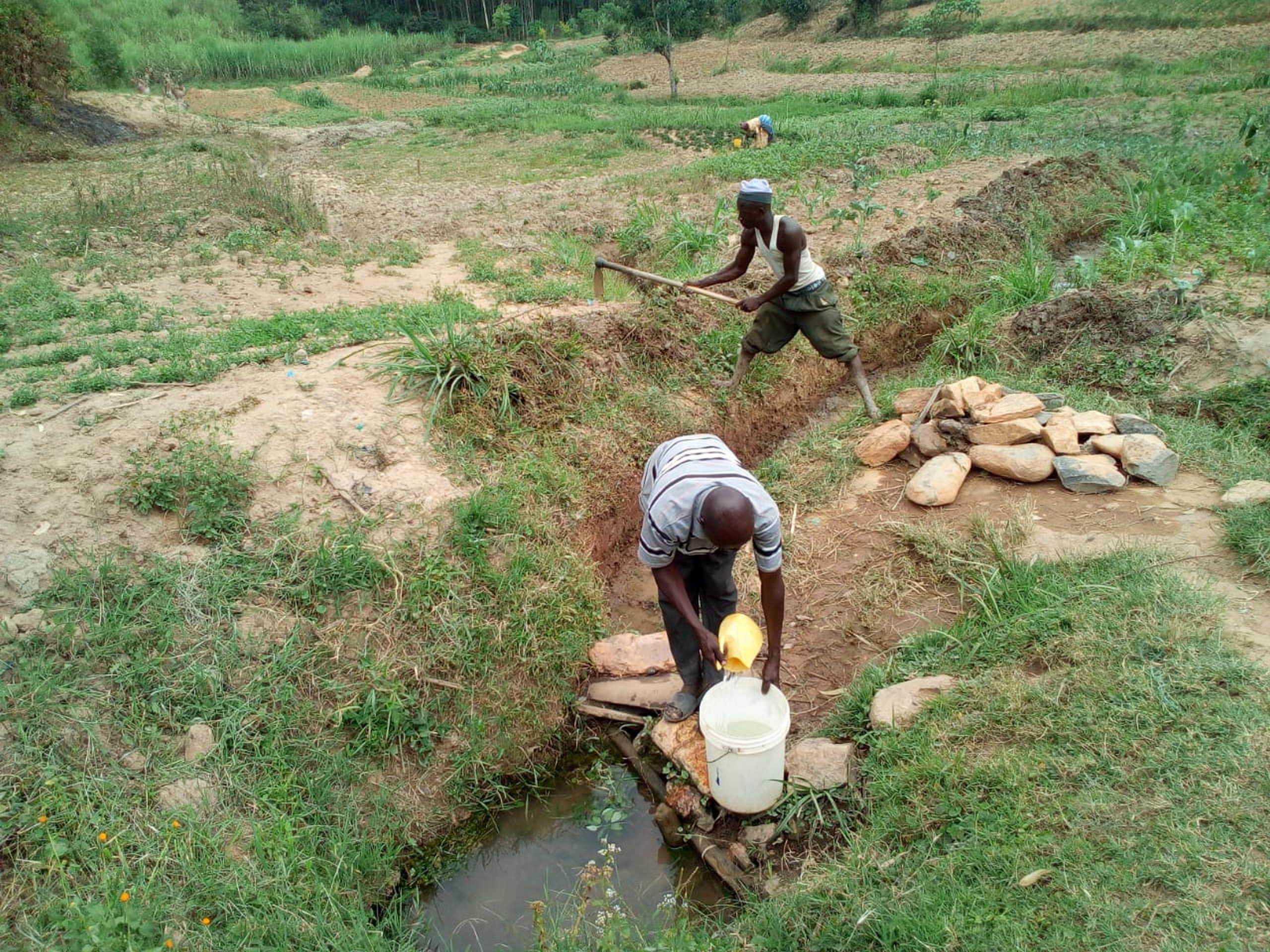 The Water Project : 5-kenya19123-fetching-water-as-the-man-behind-clears-drainage-channel-as-advised