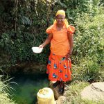 The Water Project: Chegulo Community, Sembeya Spring -  Fetching Water