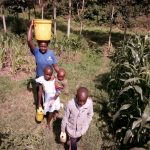 The Water Project: Mwichina Community, Shihunwa Spring -  Carrying Water Back Home