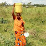The Water Project: Chegulo Community, Sembeya Spring -  Carrying Water
