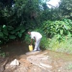 The Water Project: Kambiri Community, Sachita Spring -  Benjamin Sachita Fetching Water