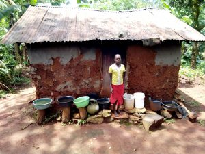 The Water Project:  Standing Outside Of Kitchen With Buckets For Collecting Rainwater