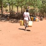 The Water Project: Kaukuswi Community -  Carrying Water Containers At Home