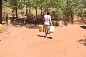 The Water Project:  Carrying Water Containers At Home
