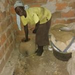 The Water Project: Nyakasenyi Byebega Community -  Fetching Water From Clay Pot At Home