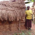 The Water Project: Nyakasenyi Byebega Community -  Woman Stands Next To Latrines