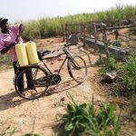 The Water Project: Kimigi Kyamatama Community -  Loading Water Containers Onto Bike