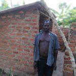 The Water Project: Rubana Yagilewo Community -  Man Poses In Front Of Latrine
