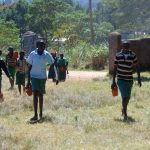 The Water Project: Bojonge Primary School -  Pupils Carrying A Brick From Home To School