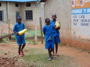 The Water Project:  Students Bringing Water To The Artisans For Mixing Cement