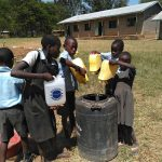 The Water Project: Khabukoshe Primary School -  Students Delivering Water For Mixing Cement