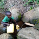 The Water Project: Chepnonochi Community, Shikati Spring -  Fetching Water