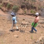 The Water Project: Kathonzweni Community -  Carrying Rocks For Dam Construction