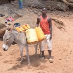 The Water Project: Kathonzweni Community -  Loading Donkey With Water