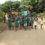 The Water Project: Lokomasama, Menika, DEC Menika Primary School -  Students Carrying Water