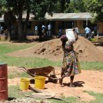 The Water Project: Koitabut Secondary School -  A Mother Carrying Water To Help Mix Cement