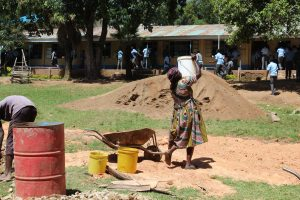 The Water Project:  A Mother Carrying Water To Help Mix Cement