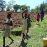 The Water Project: Kambiri Community, Sachita Spring -  Community Members Carrying Bricks To The Site